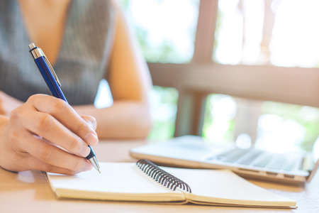 Business woman hand is writing on notepad with pen in office.On her desk there is a laptop computer. Stock Photo
