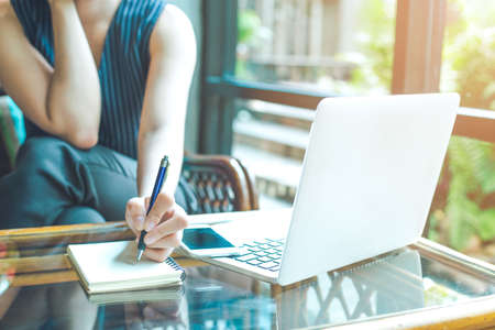 Business woman hand is writing on a notepad with a pen and using a laptop computer in the office. Stock Photo