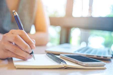 Business woman hand is writing on notepad with pen in office.On her desk there is a notebook and a mobile phone.
