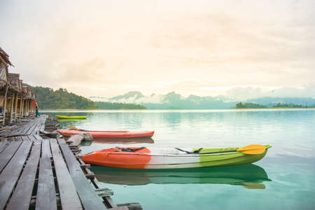 Kayak parked between the picturesque views of the mountain dam and the mist at sunrise.at Rajjaprabha Dam or Cheow Lan Dam Thailand