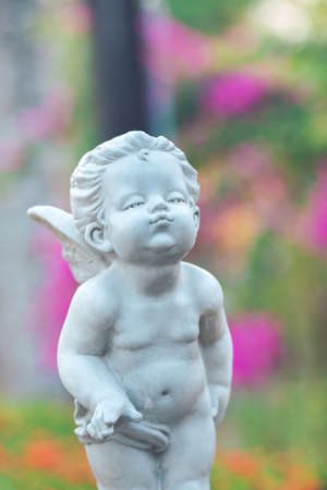 Cupid stone statue in the flower garden. Stock Photo