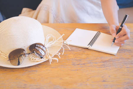 Hipster women hand in cream dresses are writing on notepad with a pen.