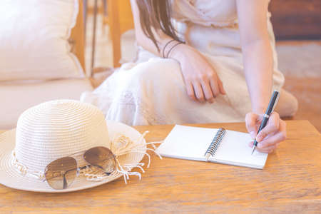 Hipster women hand in cream dresses are writing on notepad with a pen.On the wooden table there are straw hats and sunglasses.