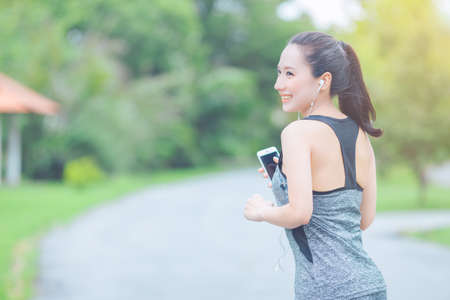portrait of a young asian woman doing outdoor exercise in park, She ran and listened to music from a mobile phone happily. Stock Photo