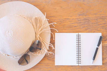 Notepad on blank screen with pen,straw hat,sunglasses on wooden desk Stock Photo