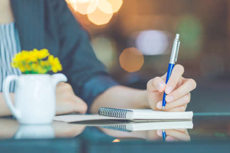 Business woman writing on a notebook with a pen in the office Stock Photo