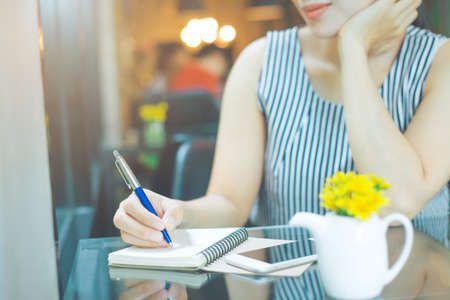 Businesswoman writing on a notebook with a pen in the blurred cafe background