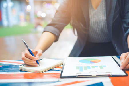 Business women take notes on business statistics and graphs. Stock Photo