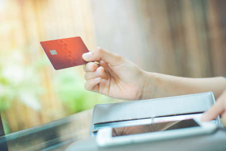 Business women hand use phones to shop online through credit cards. Stock Photo