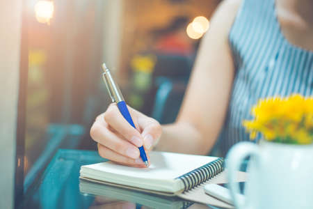 Business woman hand writing on a notebook with a pen in the office Stock Photo