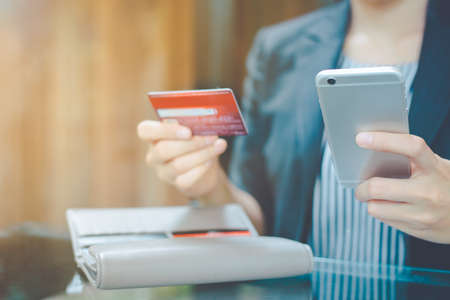 Business women hand use mobile phone to shop online through credit cards.