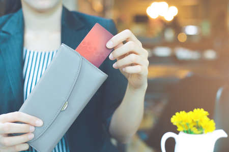 Business women hand are pulling a credit card out of a wallet.