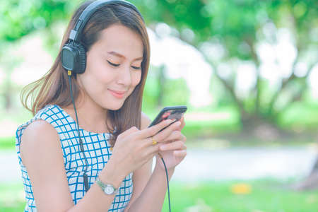 An Asian woman listening to the music with headphones in the garden.