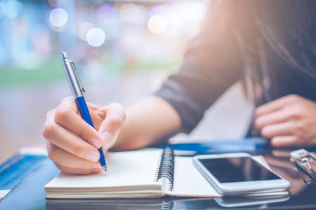 Woman hand writing on a notebook with a pen.On the table with a smartphone Stock Photo