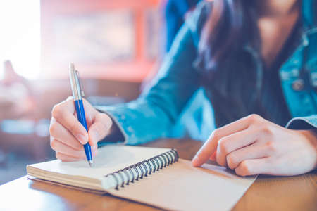 A womans hand is writing in empty spiral notepad with a pen. Stock Photo