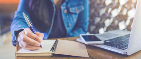 A womans hand is writing on a notepad with a pen and a phone with a laptop.Web banner. Stock Photo