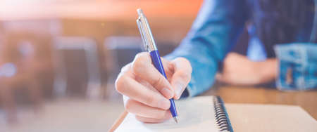 A womans hand is writing in empty spiral notepad with a pen.Web banner. Stock Photo