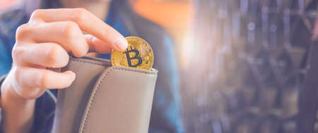 The hand of a woman is pulling a bitcoin coin out of a wallet.bitcoin digital currency,electronic virtual money for web banking and international network payment, selective.Web banner.