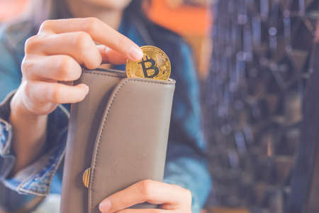 Woman hand is pulling a bitcoin coin out of a wallet.bitcoin digital currency,electronic virtual money for web banking and international network payment, selective.