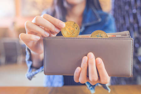 Woman hand is pulling a bitcoin out of a wallet.bitcoin digital currency,electronic virtual money for web banking and international network payment, selective.