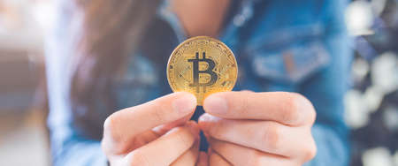 Woman hand holding a currency bitcoin.electronic virtual money for web banking and international network payment, selective.Web banner.