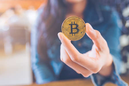 The hand of a woman holding a currency, bitcoin.electronic virtual money for web banking and international network payment, selective.