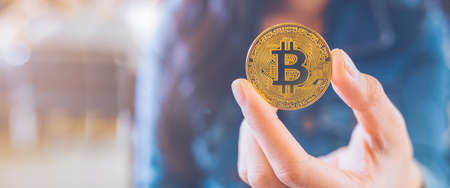 The hand of a woman holding a currency, bitcoin.electronic virtual money for web banking and international network payment, selective.Web banner.