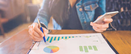 Woman hand writing on charts and graphs that show results with a pen and using a smartphone. in the office.Web banner. Stock Photo