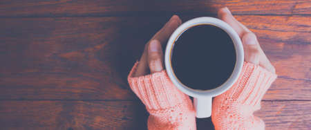Woman hand in warm sweater holding a cup of coffee on a wooden table background, top view.Web banner.