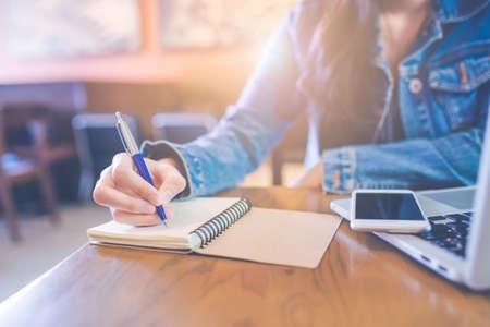 La mano de una mujer está escribiendo en un bloc de notas de espiral vacío con un bolígrafo. Sobre la mesa están los teléfonos que están en la computadora portátil.