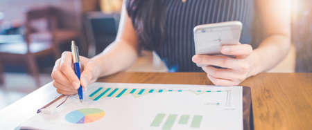 Woman hand writing on charts and graphs that show results with a pen and using a smartphone.Web banner.