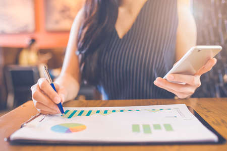 Woman hand writing on charts and graphs that show results with a pen and using a smartphone. Stock Photo