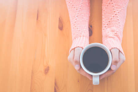 Woman hand in warm pink sweater holding a cup of coffee and heart-shaped handmade on a wooden table background, top view
