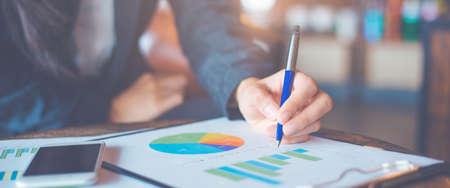 Mano de mujer de negocios escribiendo en tablas y gráficos que muestran resultados.Banner web.