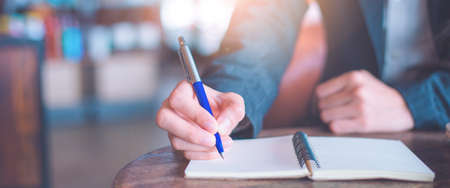 Business woman hand  writing on a notepad with a pen in the office.Web banner. Stock Photo