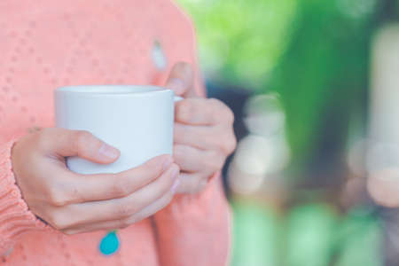 Woman holding a cup of coffee on hand