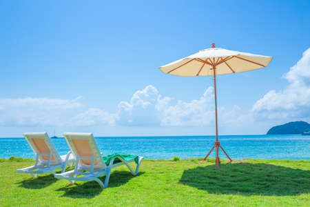 Beach chairs and beach umbrellas are on the lawn at the beach.Sea view and bright sky.