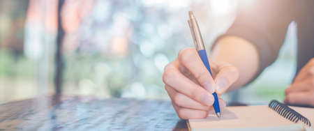 Woman hand writing on a notepad with a pen in the office.Web banner.