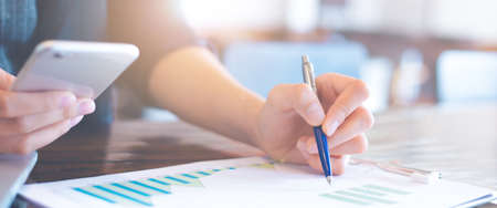 Businessman working on analysis charts and graphs showing results.Her hand holds the pen and points to the graph.Business analysis and strategy.Web banner.