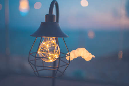 Vintage light bulbs decorated in the living room, sea view at sunset. Stock Photo