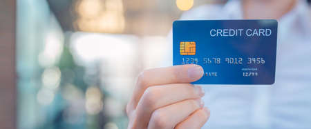 Business woman hand holds a blue credit card.Web banner.