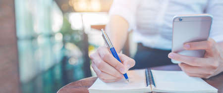 Woman hand writing on a notepad with a pen and using a mobile phone in the office.Web banner.