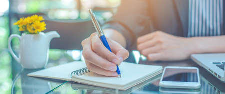 Business woman hand is writing notebook with a pen in the office.Web banner.