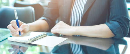 Woman writing on a notebook with a pen in the office.soft focus.Web banner. Stock Photo