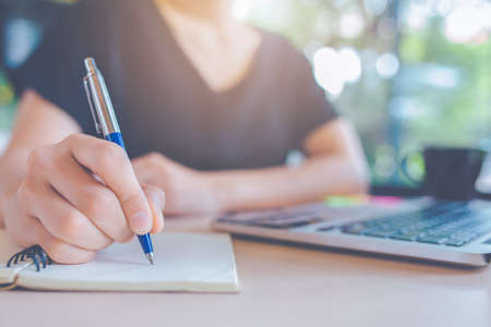 Business womans hand is writing on a notebook with a pen. Stock Photo