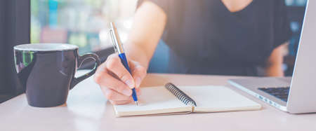 Business womans hand is writing on a notebook with a pen.Web banner.