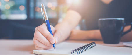Woman hand is writing on a notebook with a pen in office.Web banner. Stock Photo