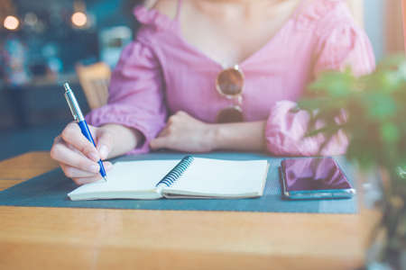 The womans hand is writing on a notebook with a pen. Stock Photo