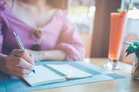 Woman hand is writing on a notebook with a pen. Stock Photo - 122844701