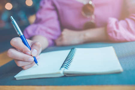 Woman hand is writing on a notebook with a pen. Stock Photo - 122844702